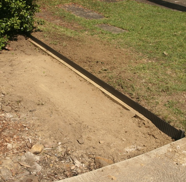The corrugated steel edging, held in place by a length of treated pine