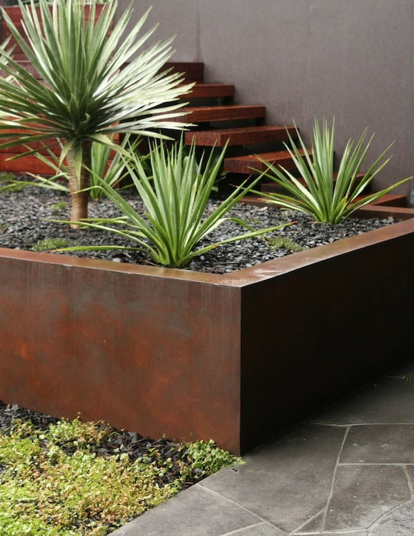 Cor-ten steel look paint finish on retaining wall warms up the surrounding greys. Design Cycas Design