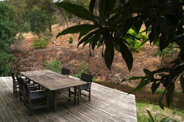 An outdoor dining area at Robert Boyle's The Falls overlooking surrounding bushland and creek
