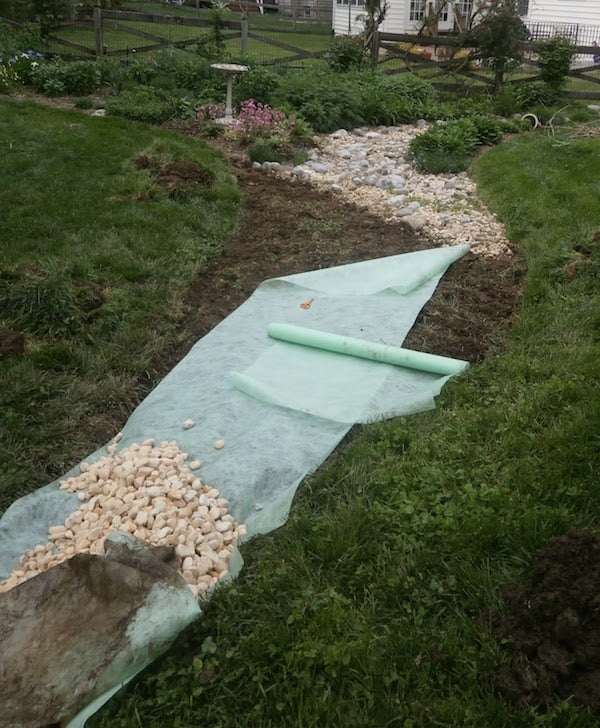 laying the river pebbles over drainage fabric