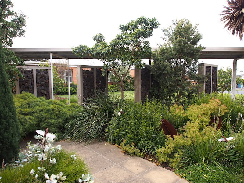 Angled gabion walls allow views in and breezeway