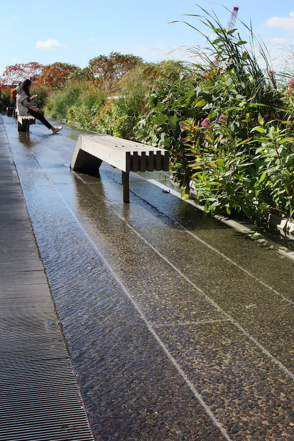 High Line NYC: a restful zone of timber loungers, movable along steel railway tracks, facing a paved area lightly washed with shallow bubbling water
