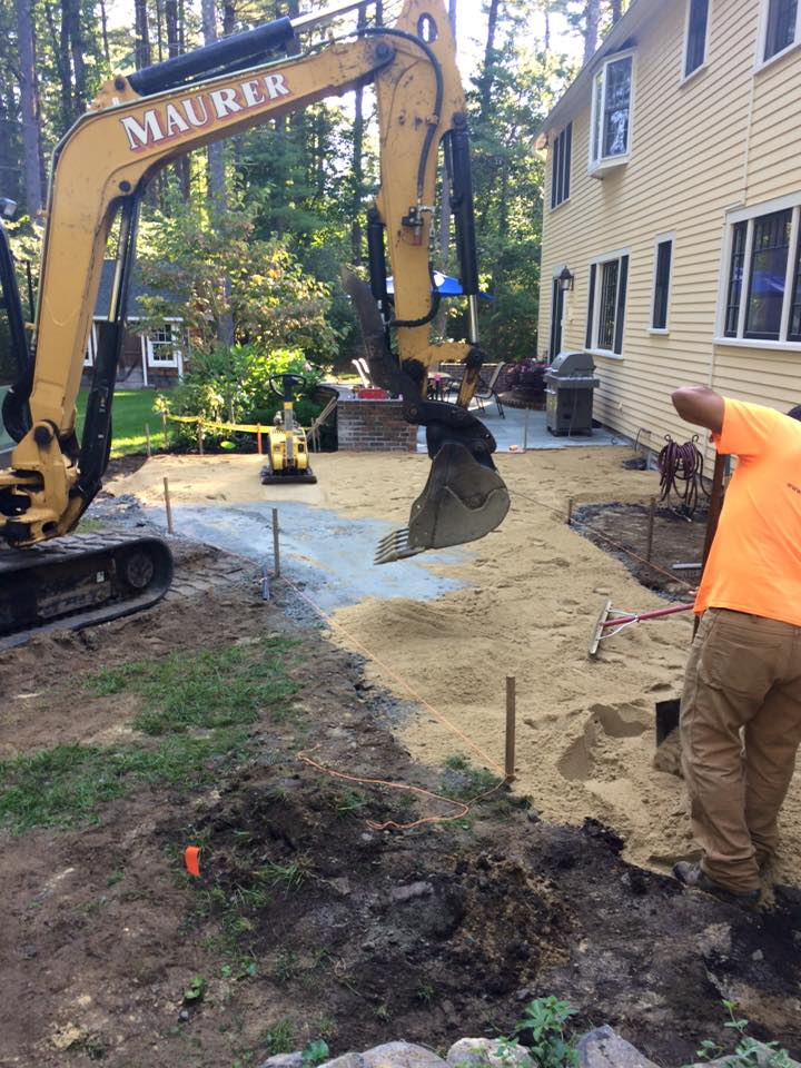 Compacting the sand layer and applying the stone dust layer for the patio and walk base