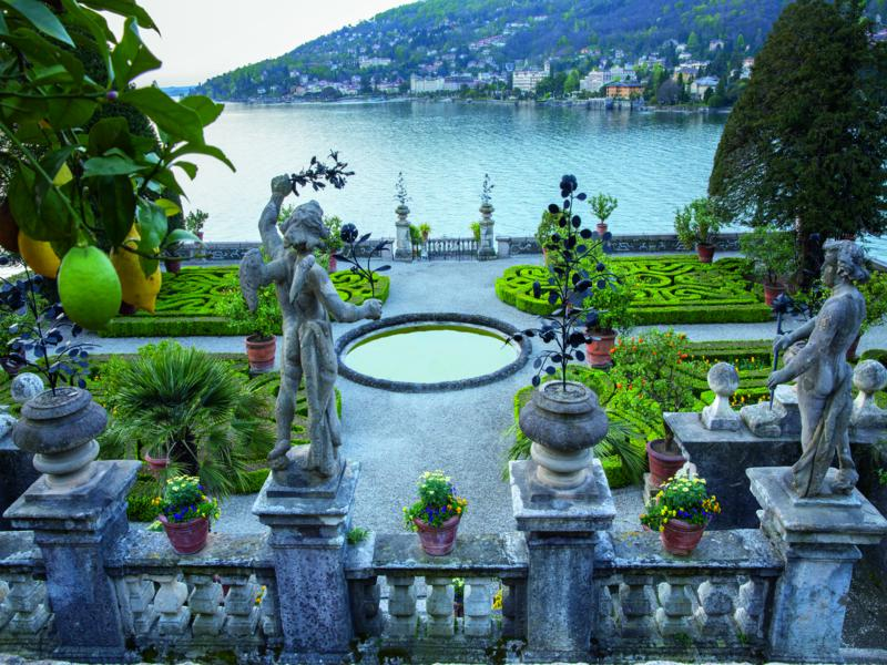 "Isola Bella, Lake Maggiore. 'Gardens of the Italian Lakes' by Steven Desmond, photography by Marianne Majerus, p32-33. ""From the platform on top of the pyramid, a sudden view opens down over the terraces to the parterre below. In the foreground, delicate ornaments of wrought iron in many forms are held aloft. Across the bay is the town of Stresa."""
