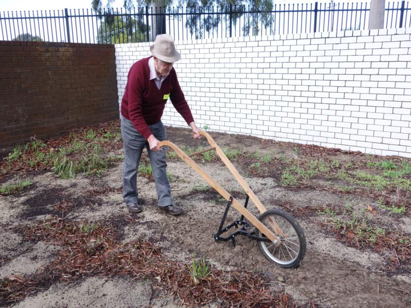 Nick Bell demonstrates the use of a hand-powered soil cultivator.